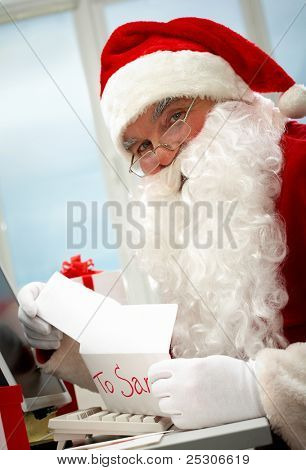 Santa holding Christmas letter and looking at camera