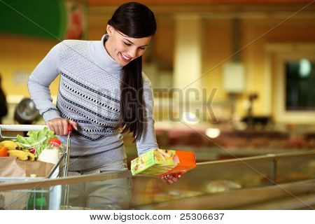 Image of pretty woman with cart choosing products in supermarket