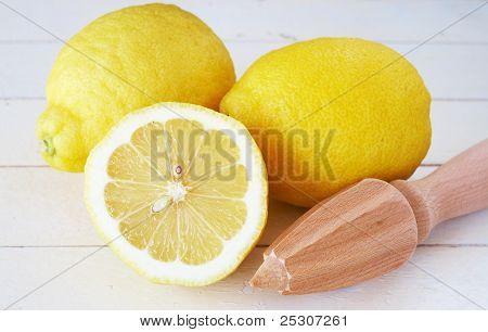 Closeup Of Three Lemons And Lemon Juicer On White