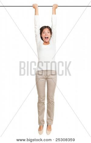 woman hanging with hands on a pole or bar. Funny image of shocked looking female model isolated on white background.