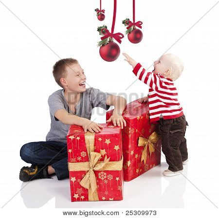 Christmas Baby Boy With Gift Box. He Is With His Brother