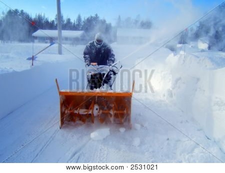 Man Cleaning Driveway With A Snowblower