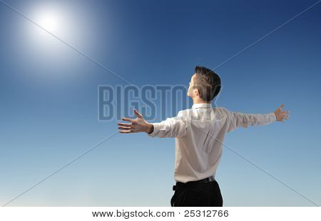 Businessman stretching out his arms in front of the sun