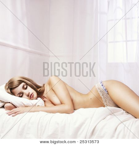 Fashionable photo sleeping nude woman in a white room