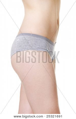 Site view of a fit young girls belly, hips and wills, dressed in underwear, isolated on a white background.