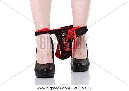 Front view of long sexy feet in black high heels, and thongs being taking off of the legs, isolated on white background.