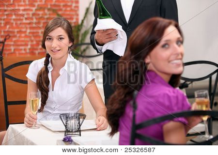 two women drinking sparkling wine at restaurant