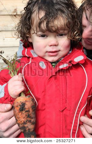 Little boy holding organic carrot