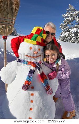 Father and daughter building snowman
