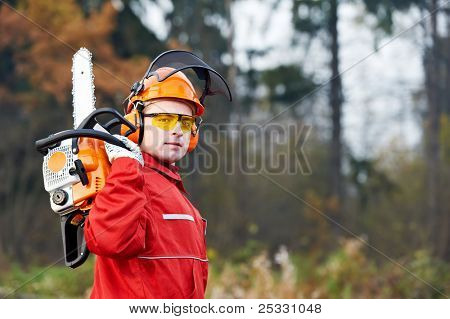 Lumberjack Worker in protective safety work wear With Chainsaw at Forest
