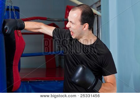 Boxer Agressively Punching A Sand Bag