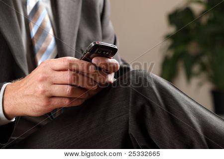 Mensajes de texto o consultar el correo electrónico en el teléfono móvil mientras que a la espera de una reunión de negocios