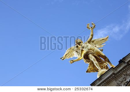 Angel on the roof of the Petit Palais in Paris France against a clear blue sky