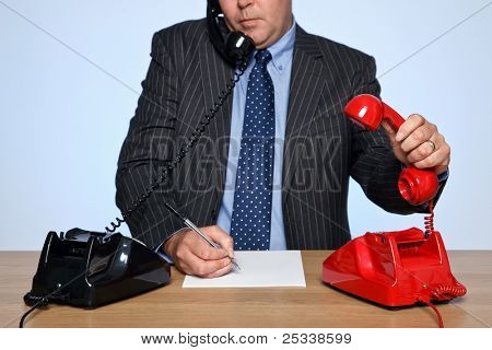 Photo of a businessman sat at a desk with two traditional telephones, one red and one black. He is listening to one call whilst picking up the other phone.