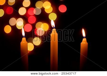 burning candles with defocussed Christmas lights behind