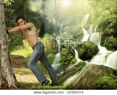 Porträt eines schönen jungen muskulösen Mannes an einem Baum an einem schönen, himmlischen Ort gelehnt