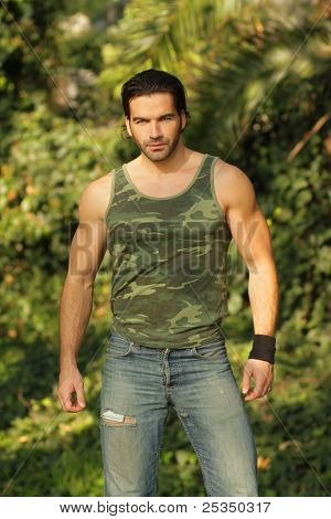 Portrait of a relaxed casual muscular young man in beautiful natural setting