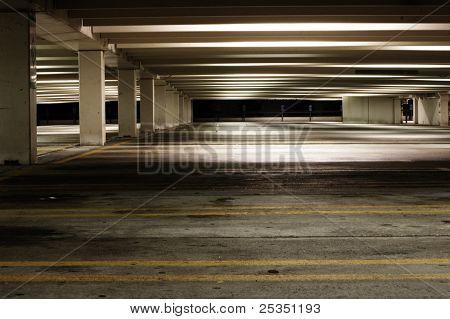 Empty parking garage at night, dirty and dark.