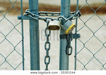 Chain link fence locked with pad locks.