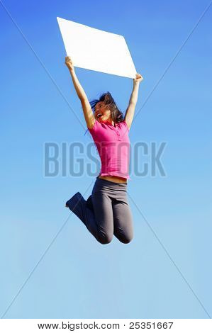 Chinese girl jumping with sign in front of a big blue sky.