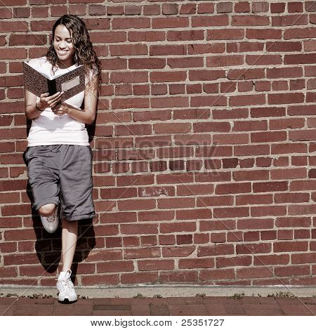 Beautiful young girl reading notebook against a brick wall.