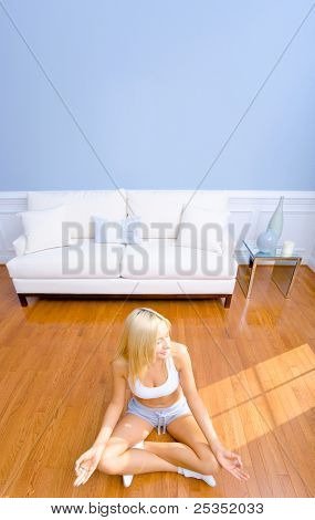 Young woman sitting cross legged on floor with hands on knees meditating. Vertical shot.