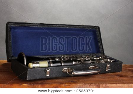 old clarinet in case on wooden table on gray background