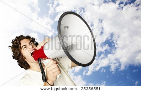 portrait of young man shouting with megaphone against a blue sky background