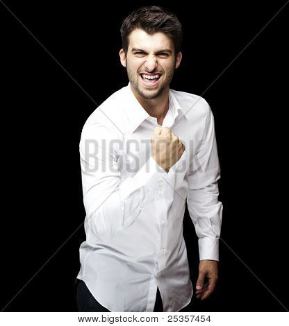 portrait of young man winner gesture against a black background