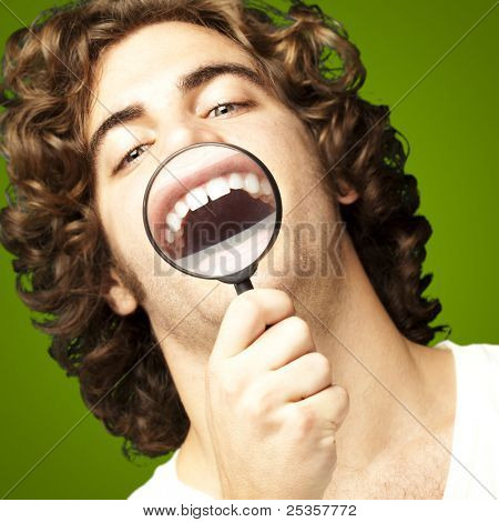 portrait of young man with magnifying glass showing his teeth over green background