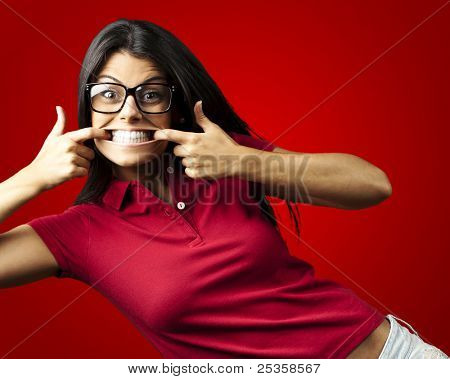portrait of happy young woman doing a grimace over red background