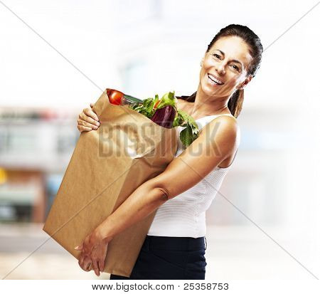 portrait of middle aged woman holding the purchase at a crowded place