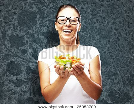 portrait of middle aged woman holding salad against a vintage wall