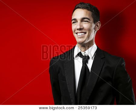 portrait of young business man smiling against a red background