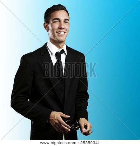 portrait of young business man holding a sunglasses on a blue background