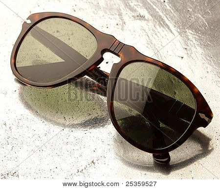 modern sunglasses on a metal surface