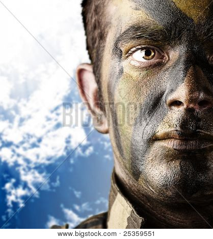 portrait of young soldier painted with jungle camouflage against a blue sky background
