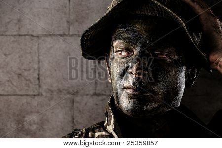 portrait of young soldier face painted with jungle camouflage against a grunge bricks wall