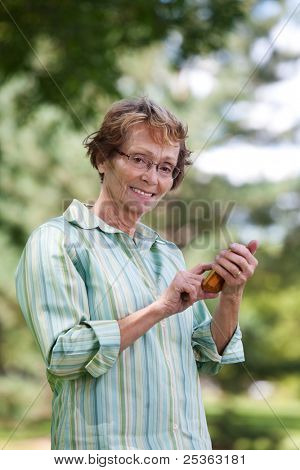 Portrait of smiling senior woman text messaging in park