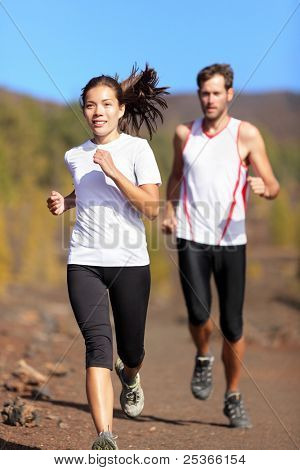 Young couple running together outdoors in beautiful volcanic landscape. Woman trail runner training for marathon run with male model jogging in background.