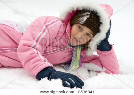 Cheerful Girl Laying In The Snow