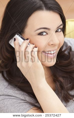 Beautiful happy young Latina Hispanic woman smiling and talking on her cell phone at home on her sofa