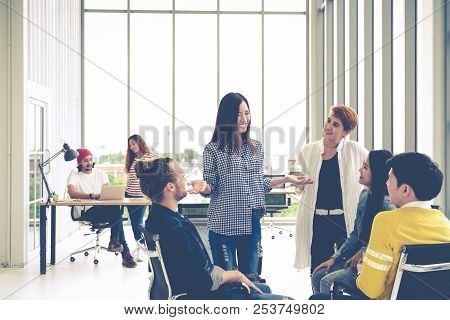 poster of Group Of Young Multiethnic Creative Team Engaged Brainstorm In Small Meeting While Standing, Sitting