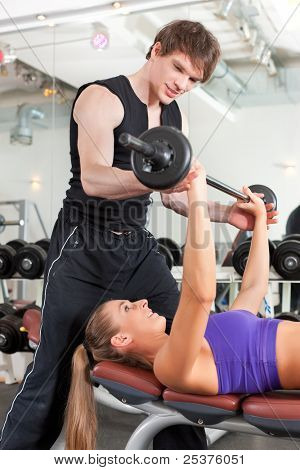 Young couple exercising in gym with weights; the man seems to be the personal trainer