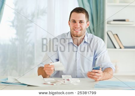 Young businessman with pocket calculator checking bills