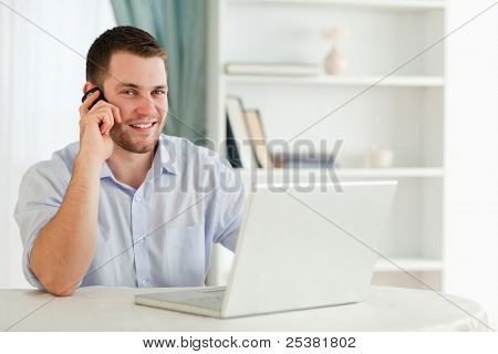Smiling young businessman on the phone in his home office