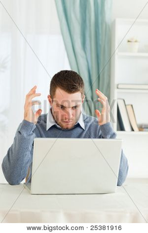 Young businessman having problems with his laptop in his home office