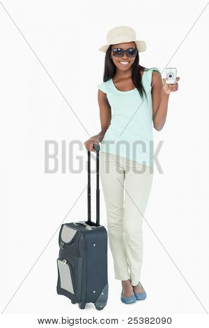 Smiling young woman making holidays abroad against a white background