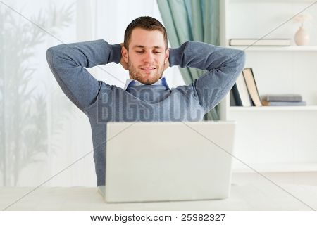 Young businessman leaning back in his home office