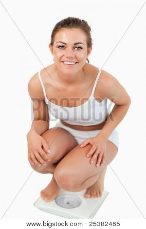 Portrait of a fit woman squatting on scales against a white background